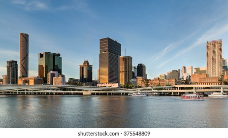 BRISBANE, AUSTRALIA - OCT 24, 2014: Wide angle panorama at sunset of the Brisbane city skyline, Victoria Bridge and the Riverside Expressway. City Hopper ferry on the river leaving North Quay terminal