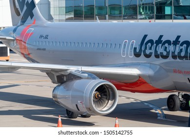 Brisbane, Australia - Sept 15 2019: Side, wing and engine of a Jetstar Airbus A320 docked at terminal gate on tarmac at Brisbane airport plane.