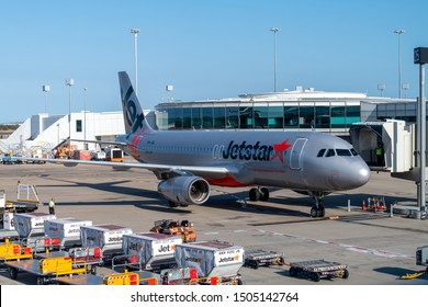Brisbane, Australia - Sept 15 2019: Jetstar Airbus A320 airliner docking at terminal gate on tarmac at Brisbane airport plane ready for unloading and loading of cargo and luggage