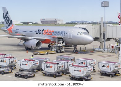 Brisbane, Australia - September 27, 2016: View of baggage trucks waiting to offload passengers' luggage to Jetstar aircraft at Brisbane Airport during daytime.