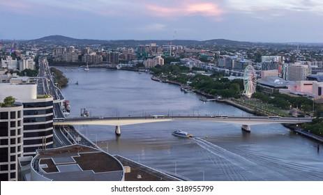 Brisbane City Beautiful Panorama Aerial View of Boat cruise under Go Between Bridge (Hale Street Link) over Brisbane River, Cityscape at Dusk in Summer, Queensland, Australia