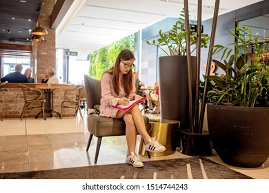 Brisbane, Queensland, Australia: 24th September 2019: A young Asian girl studiously writes in her folder while sitting in a busy shopping centre
