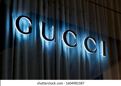 Brisbane, Queensland, Australia - 27th November 2019 : View of the Illuminated Gucci sign on a glass wall with blue curtain in Brisbane. Gucci is know for his luxury leather and fashion goods.