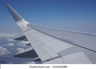 Brisbane, Queensland / Australia - January 15 2019: Airplane wing of an Airbus 321 above the clouds and flying over Brisbane City
