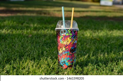 Brisbane, Queensland / Australia - July 26th 2019: Cherry Slurpee close up from Seven Eleven(7-Eleven) on the grass