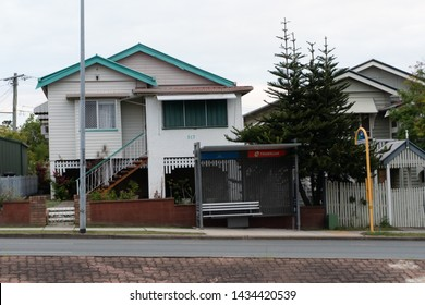Brisbane, Queensland / Australia - June 26th 2019 : Queenslander white wooden house (architecture) in front of a bus stop in Greenslopes