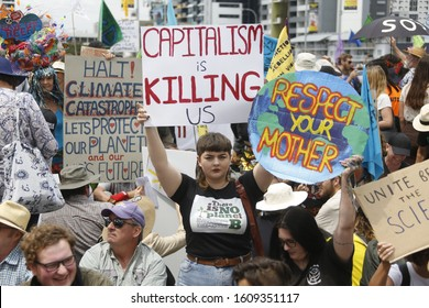 "Brisbane, Queensland / Australia - October 11, 2019: Woman holding ""Capitalism is killing us"" sign at Extinction Rebellion protest on William Jolly Bridge"