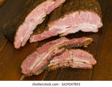 Brisket. Classic NYC delicatessen beef brisket a butcher shop favorite. Dry rubbed w/ spices & seasonings, slow cooked in a smoker w/ mesquite wood chips. Sliced beef brisket on wooden butchers shop.