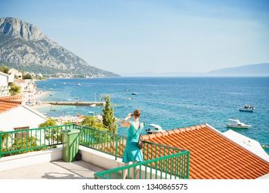 Brist, Dalmatia, Croatia, Europe - A woman taking a picture of the beautiful bay of Brist