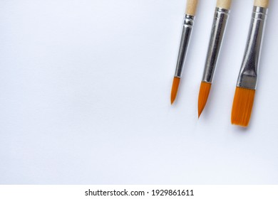 Bristle brushes for coloring and painting with paints with copy space. Tassels for paints on a white paper background close-up with a place for the text.