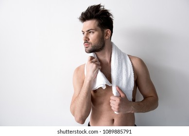 Bristled guy with tousled hair is standing and holding white towel over his neck. He is looking aside seriously. Copy space in the left side
