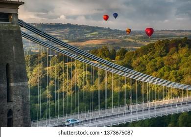 Bristol, Avon, England, Britain, August 2014, hot air balloons part of International Bristol Balloon Fiesta floating over valley with Clifton suspension bridge in foreground