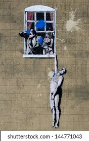 "BRISTOL, ENGLAND - JUL 3- 2013 - A mural named ""Naked Man"" by street artist Banksy on a wall in Park Street, Bristol on 3 Jul 2013. Painted in 2006 it is now firmly part of the Bristol tourist trail."