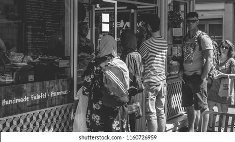 Bristol, England - July 14, 2018: Diversity in Britain, People ordering food, black and white street photography