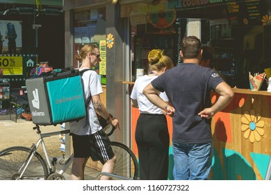 Bristol, England - July 14, 2018: City Life in Bristol, Deliveroo Cyclist ordering a food, shallow depth of field