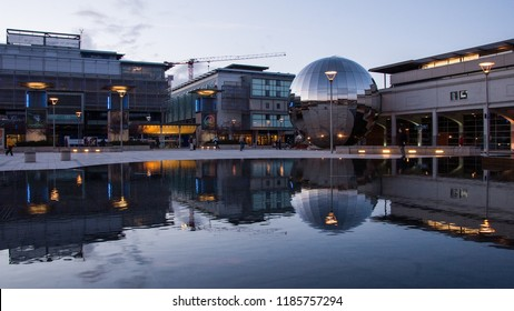 Bristol, England, UK - December 2, 2016: The At-Bristol Planetarium and other buildings are reflected in water features in Bristol's Millennium Square during regeneration of the city's Harbourside.