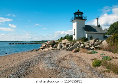 Bristol Ferry lighthouse is surrounded with large boulders to protect the keepers when the tides would rise in Narragansett Bay in Rhode Island. Beach area is covered with open shells at low tide.