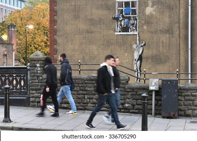 BRISTOL - OCT 31: People walk past the famous Banksy graffiti piece Naked Man on a city centre building on Oct 31, 2015 in Bristol, UK. Banksy is an internationally renowned street artist.