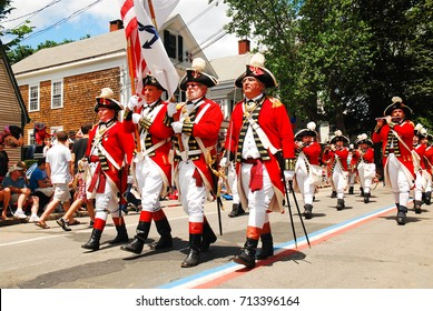 Bristol, RI, USA July 3, 2009 Adults dressed in British red coats from the American Revolution, march in a fourth of July parade in Bristol, Rhode island