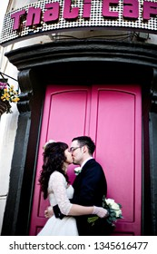 Bristol, UK - 03/03/2009: Bride and groom portrait of the couple dancing to celebrate their unique, creative and quirky wedding day outside the Thali Cafe with colourful pink doors