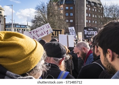 Bristol, UK - 04 February 2017:  Crowds of people wave banners and march through the city of Bristol, UK, protesting against the policies of Donald Trump, and his proposed state visit to the UK.