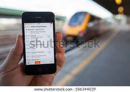 BRISTOL, UK - APRIL 8, 2014: A male hand holding an iPhone at Bristol railway station with a train in the background. The smart phone displays live train travel information on the Train Times App.