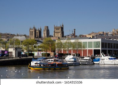 BRISTOL, UK - APRIL 8, 2019. Bristol Cathedral founded in 1140 and cityscape seen from Bristol Harbour with ferry boat. Bristol, England, UK, April 8, 2019