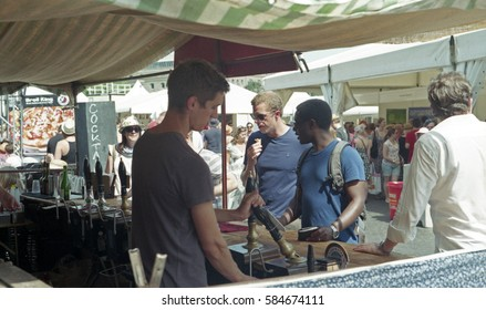 Bristol, UK - July 13, 2013: Bristol Foodies Festival: young man pulling pints at beer tent, customers waiting to be served and crowds and stalls behind.