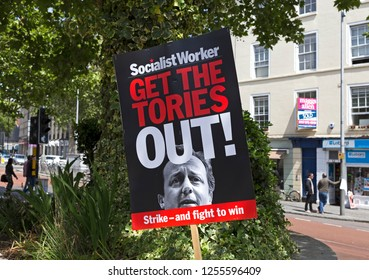 """BRISTOL, UK - MAY 30, 2015: A placard with the slogan """"GET THE TORIES OUT"""" and a photograph of prime minister David Cameron at a demonstration shortly after the 2015 general election."""