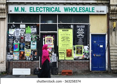 BRISTOL, UK - OCT 31, 2015: A woman in Islamic hijab attire walks past a derelict shop building. The English west country city houses a large proportion of the UK's migrant and refugee population.