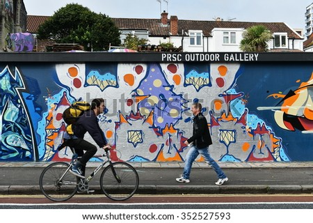BRISTOL, UK - OCT 31, 2015: People pass a graffiti piece on a wall in the city centre. The west country city is famous for its vibrant graffiti and street art.