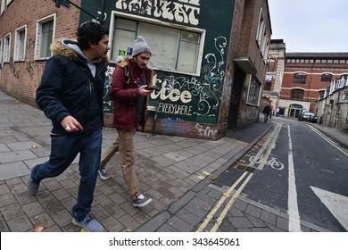 BRISTOL, UK - OCT 31: People walk past graffiti on a wall in the city centre on Oct 31, 2015 in Bristol, UK. The west country city is famous for its graffiti and street art.