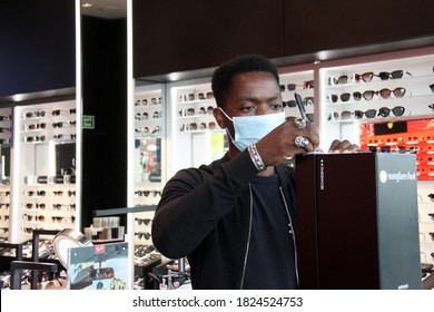 Bristol, UK September 29, 2020: young black male retail assistant at work in Sunglasses shop wearing face covering