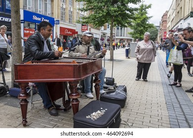 Bristol, United Kingdom - 29 July 2016:  Street musicians perform for visitors and tourists on a high street in Bristol city centre, UK.
