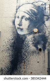 Bristol,UK-25 February,2016: graffiti of the street artist Banksy named 'Girl with Pierced Eardrum',inspired by the famous painting by Dutch painter Johannes Vermeer 'Girl with Pearl Earring'