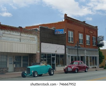 BRISTOW, OKLAHOMA—JUNE 2016: Classic cars parked infront of old brick buildings catch the attention of motorists along Route 66 in Bristow, Oklahoma.