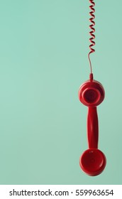 A British 1960s to 1970s style retro red telephone receiver, facing front and hanging by spiral cord against aqua background with copy space on left side.