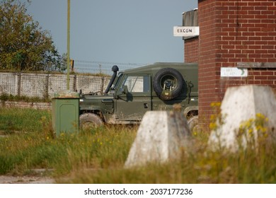 a British Army Land Rover Defender infantry vehicle parked in a secure military compound