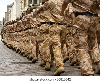 British Army soldiers marching in desert camouflage uniform.