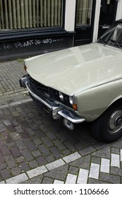 A British automobile from the 1960's parked on a European city street