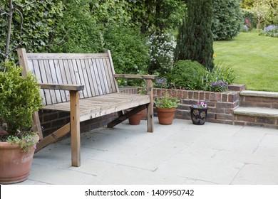 Jardín trasero británico con patio pavimentado y banco tradicional de madera