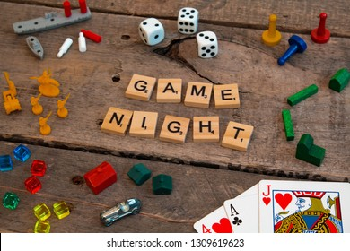 "British Columbia, Canada, - February 01, 2019 - ""Game Night"" made from Scrabble game letters, Risk, Battleship pieces, Monopoly, Settler of Catan and other game pieces"