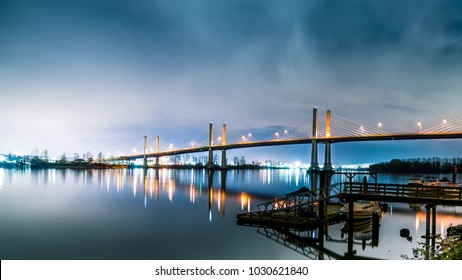 British Columbia - Canada. The Golden Ears Bridge, connecting Maple Ridge to Langley. Long exposure at night, Sky and bridge reflecting into Fraser River.