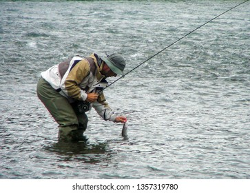 British Columbia, Canada - November 8 2018: Adult man is fishing and holding the fish with his hands in the lake.
