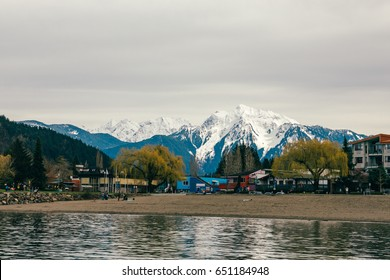 British Columbia lake with mountains in the background and a small town.