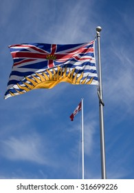 British Columbia provincial flag flying in foreground with Canada flag in distance.  flag poles, blue sky. BC flag includes setting sun, wavy blue lines symbolizing ocean, Union Jack