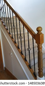 British Craftsmanship, Solid Oak and Iron interior stairwell and Banister with carpeted stairs and clean white surrounding.