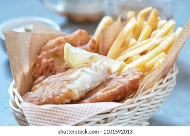 British crispy fish and chips - fried cod, french fries, lemon slices and tartar sauce