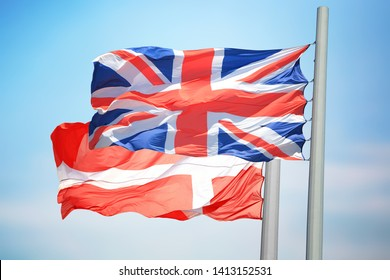 The British and Danish flags against the background of the blue sky