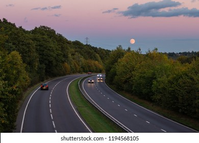 British dual carriageway road during sunset with rising full moon in the background